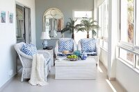 Comfortable wicker furniture, blue and white accessories and two potted palms in bright loggia