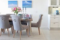 Elegant upholstered chairs, lilies and crockery on table in elegant dining area