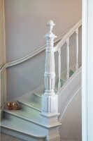 White-painted winding staircase with carved newel post