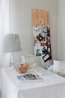 Table lamp and wooden bowl on table with white tablecloth next to wooden board leant against wall and used as pinboard