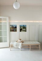 Sun hat and blanket on couch below string of fairy lights and photos hung on wainscoting