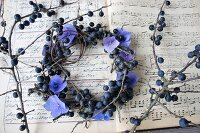 Wreath of hydrangea flowers and sloe branches on old sheet music