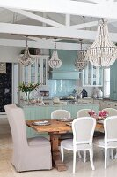 Chandelier above dining set with Rococo-style chairs around solid wood table in front of open-plan kitchen