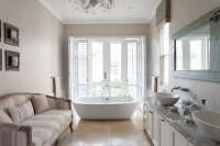 Comfortable sofa in spacious bathroom with free-standing bathtub in front of French windows in background
