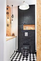 Custom chipboard bathroom with chequered floor and black toilet