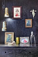 Black-painted chipboard panels on walls and kitchen cupboards, religious icons and pendant lampa