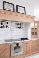 Pale wooden kitchen counter with wooden, profiled mantel hood above cooker