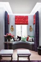 Stools with pale seat cushions opposite scatter cushions arranged on window seat in bay window with red Roman blinds