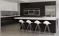 Designer bar stools with white shell seats at island counter with black base unit in front of fitted cupboards with integrated kitchen appliances