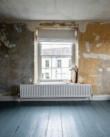 Soft toy and radiator in front of lattice window with Roman blind in room with patinated wall and blue-grey wooden floor