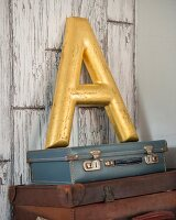 Gilt decorative letter A on stack of vintage suitcases leaning against peeling board wall