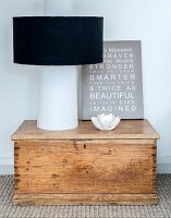 Modern lamp and picture with motto on top of vintage wooden trunk