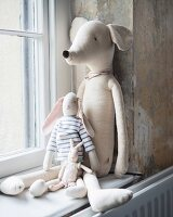 Various soft toys sitting on window sill leant against wall with vintage patina