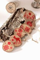 Garland of wooden discs stamped with red festive motifs