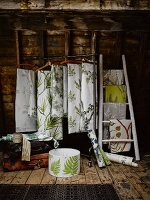Lengths of fabric with various patterns of leaves hanging from clothes rack and ladder