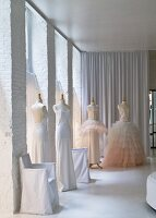 Elegant white dresses on tailors' dummies in white loft interior with floor-length curtains in background