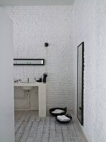 Washstand against whitewashed brick wall and baskets on towels on wooden floor in ensuite bathroom
