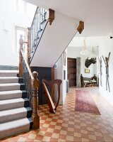 Runner on vintage chequered floor in foyer; staircase to one side with carved newel posts