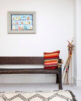Striped cushion on antique bench next to decoratively painted walking sticks and below framed picture