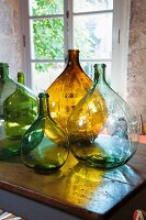 Demijohns of various colours on table