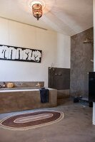 Ethnic-style bathroom with grey-rendered walls, masonry bathtub and open-plan shower area