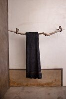 Grey towel on driftwood towel rail mounted on wall