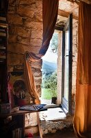 French window with view of mountain landscape in stone wall