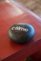 Black stone decorated with lettering reading 'calme' on red-painted table