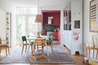 Tripp Trapp highchair and retro chairs around white table on rug in rustic dining room: dusky-pink fitted kitchen in background