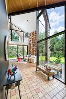 Spacious interior with tiled floor and black console table opposite glass facade with view into sunny garden