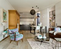 Kitchen counter and mixture of retro and modern furnishings in open-plan living-dining area