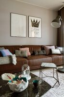 Large leather sofa with various scatter cushions and two, stone-topped coffee tables