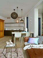 View across sofa to ining table and delicate animal figurines in kitchen integrated unobtrusively into living area