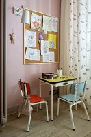 Retro children's furniture (table and chairs) below children's drawings on large pinboard next to bird-patterned curtain