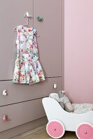 Summer dress hanging on lilac fitted wardrobe with animal-shaped handles