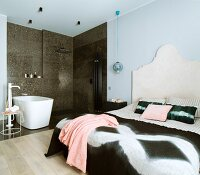 Large bed with curved headboard in bedroom and free-standing bathtub in open-plan bathroom area