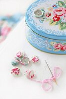 Romantic tin with pastel pattern of roses and lace, fabric-covered buttons and needle and thread