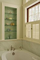 Elegant, country-house bathroom with marble cladding; ornaments on glass shelves in niche with shimmering mosaic tiles
