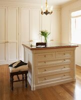 Elegant dressing area with fitted wardrobes, chest of drawers and exotic wood parquet floor