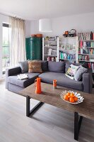 Coffee table with orange accessories, lilac-grey corner couch and simple bookcase in background
