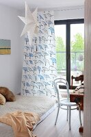 Futon in front of bird-patterned curtain on French doors, paper star and white, bentwood chair