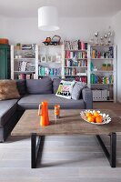 Modern coffee table with orange accessories, corner sofa and white-painted bookcases
