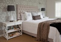 Double bed with button-tufted headboard against grey and white patterned wallpaper flanked by table lamps on bedside tables