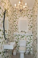 Guest toilet with floral wallpaper and traditional chandelier