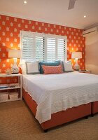 Twin box spring beds with orange fabric covers pushed together with white bedspread below window in wall with orange and white patterned wallpaper