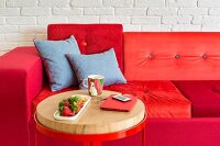 Sofa with cushions in various shades of red and side table with round metal frame and wooden top
