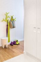 Green, stylised tree as coat rack and designer stool in hallway with fitted cupboards