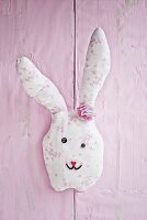 Hand-sewn fabric rabbit on pink wall