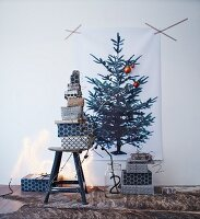 Stacked gifts wrapped in black and white paper below Christmas tree print on wall