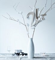 Delicate, white paper flowers on dry branches in porcelain vase